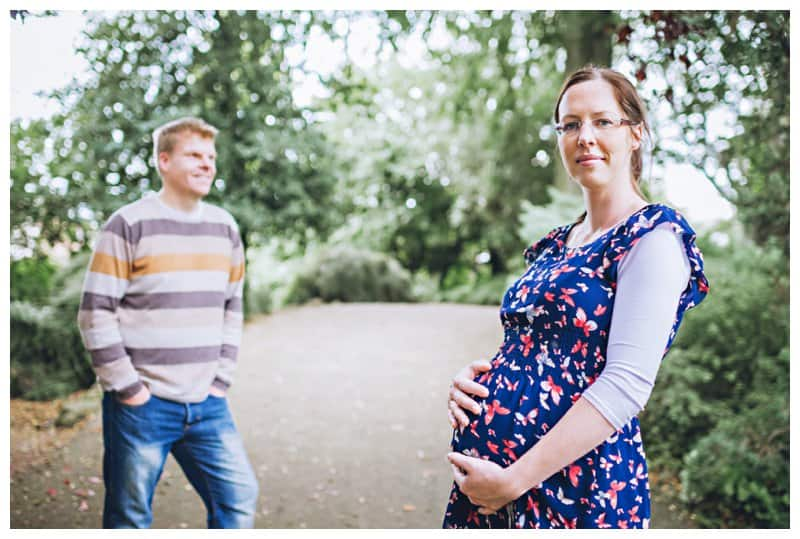 Casual shot of a young pregnant couple in the park in Leamington