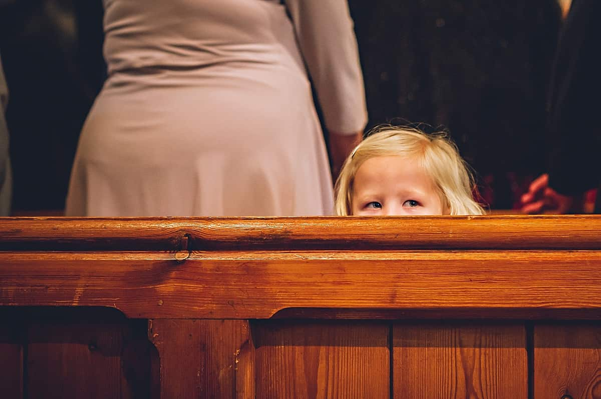 Little girl hiding behind church pew.