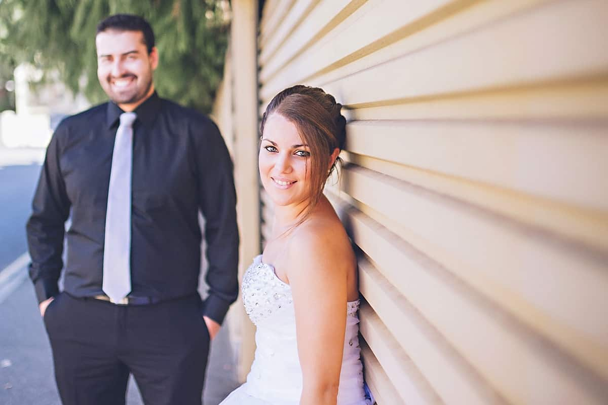 Bride leaning against garage door with groom in background smiling