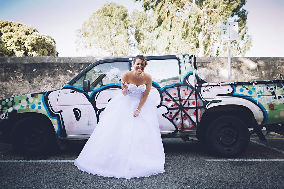 Bride standing in front of graffiti pained car laughing!