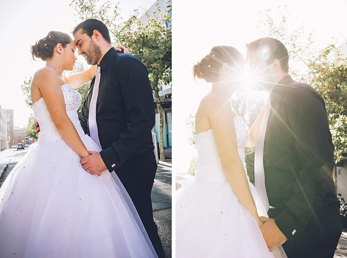 Colour image of the bride and groom holding each other with the sun backlighting them.