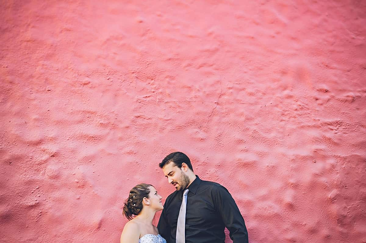 bride and groom looking into each others eyes in front of a bright red wall.