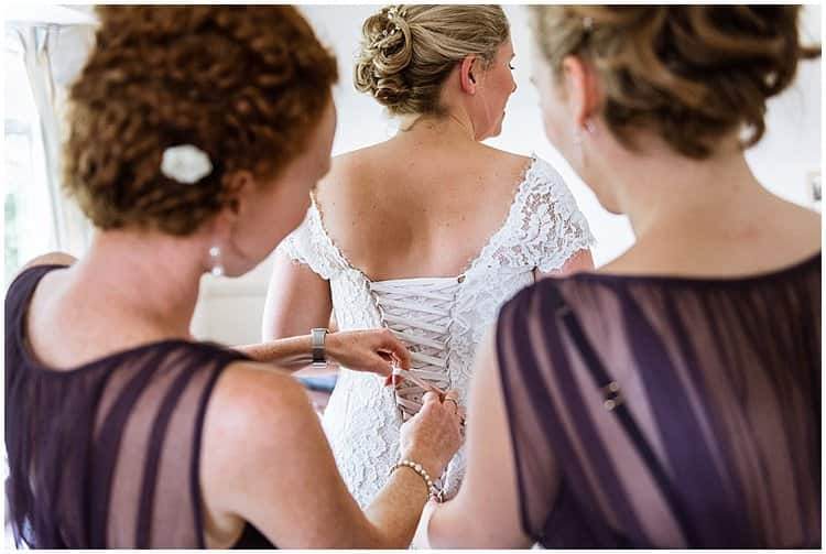 Bride having her wedding dress laces done