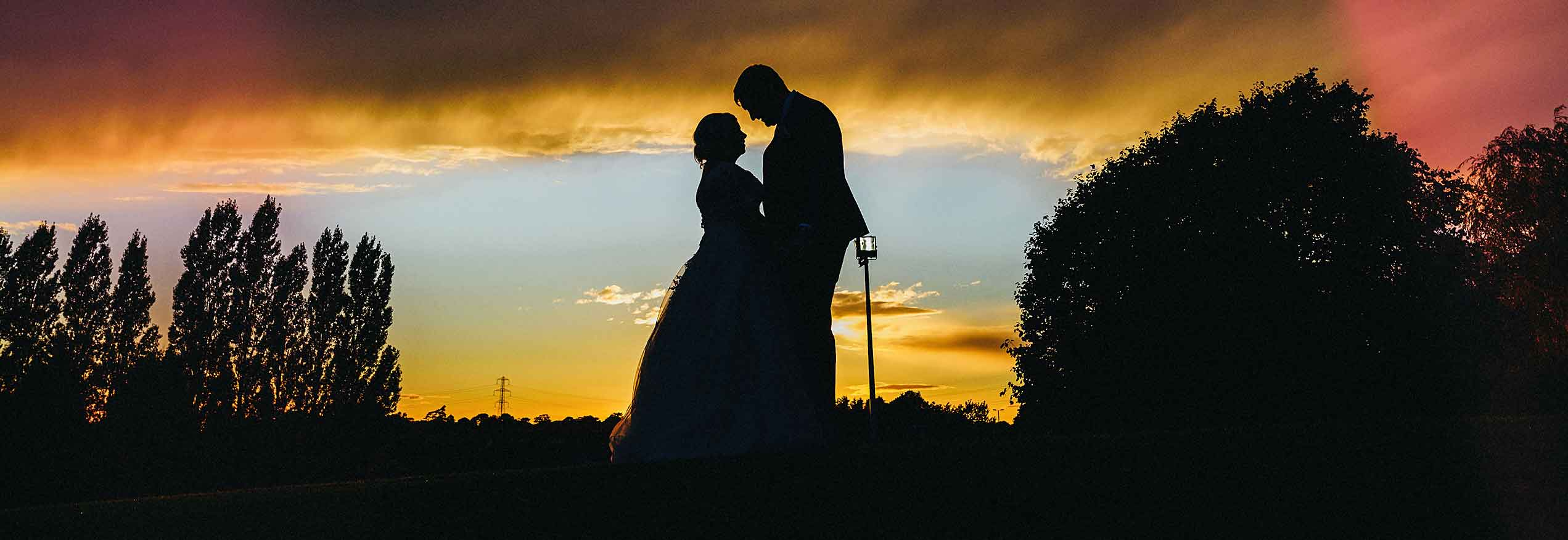 Bride and Groom silhouetted against a sunset - wedding prices